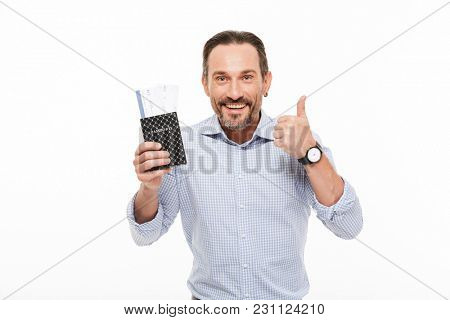 Portrait of a happy mature man dressed in shirt holding passport with flying tickets and showing thumbs up gesture isolated over white background