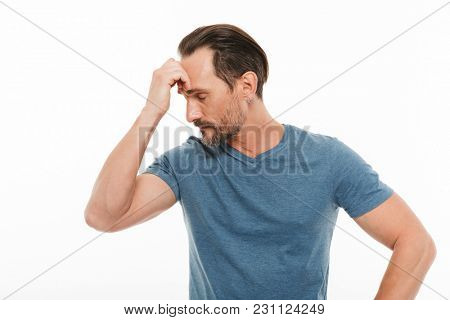 Portrait of a pensive mature man dressed in t-shirt looking away isolated over white background