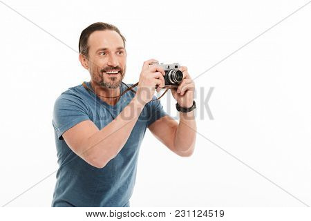 Portrait of a happy mature man dressed in t-shirt holding photo camera and looking away at copy space isolated over white background