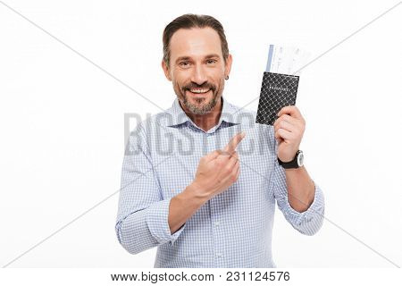 Portrait of a happy mature man dressed in shirt pointing finger at passport isolated over white background