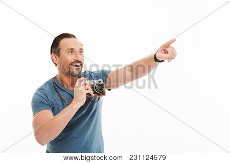 Portrait of a cheerful mature man dressed in t-shirt holding photo camera and pointing finger away isolated over white background
