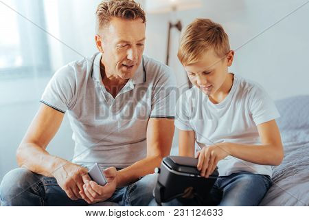 Modern Developments. Cheerful Nice Smart Boy Sitting Together With His Father And Holding 3d Glasses