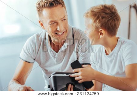 Futuristic Technology. Smart Positive Curious Looking At His Father And Talking To His While Discuss