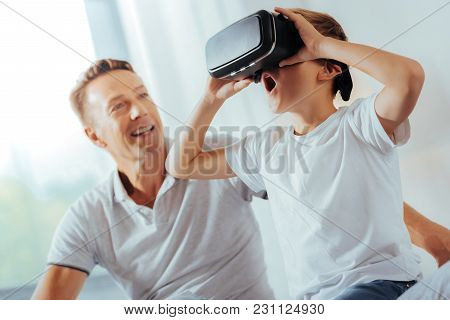 So Realistic. Delighted Positive Surprised Boy Wearing 3d Glasses And Looking Into Them While Enjoyi