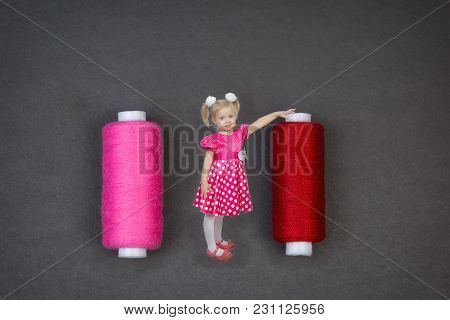 A Beautiful Girl In A Pink Dress Laid Her Hand On A Huge Coil With Thread For Sewing.