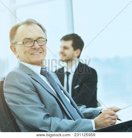 Portrait Of A Successful Businessman In The Office On The Background Of Working Business Team In A M