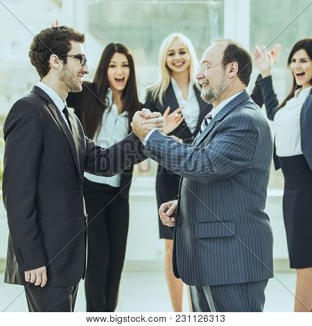 Handshake Of Business Partners On Background Of Cheering Business Team .the Photo Has A Empty Space