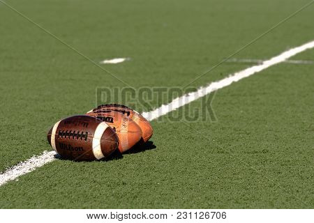 Illustrative Editorial Image Of Three Wilson Footballs On An Artificial Turf Football Field With Dia