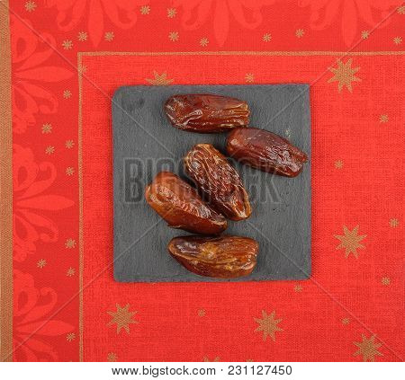 Colorful And Crisp Image Of Dates On Slate And Christmassy Napkin