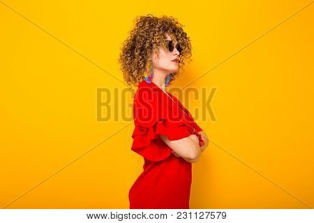 Portrait Of A White Woman With Afrro Curly Hairstyle In Red Dress And Sunglasses Standing Sideways W