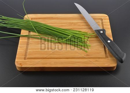 Colorful And Crisp Image Of Chives With Table Knife And Cutting Board On Black