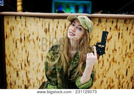 Military Girl In Camouflage Uniform With Revolver Gun At Hand Against Army Background On Shooting Ra
