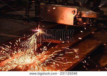 Worker Cutting Steel Plate With Acetylene Welding Cutting Torch And Bright Sparks In Steel Industry.