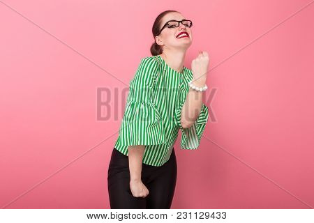 Portrait Of Attractive Businesswoman With Hair Bun In Striped Blouse And Eyeglasses Holding Her Fist