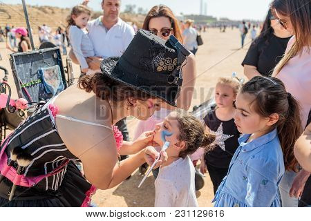 The Participant Of The Purim Festival Dressed In Fabulous Costume, Puts A Drawing On The Girl's Face