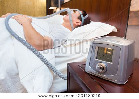 Cpap Machine Sitting On A Bedside Table With Blurred Middle Age Asian Man Sleeping In His Bed Wearin