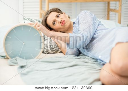 Young And Angry Woman Turning Off A Big Alarm Clock Lying On The Comfortable Bed At Home