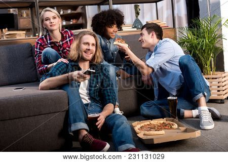 Multicultural Friends Watching Tv And Eating Pizza At Home