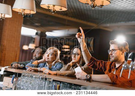 View Of Young Friends At Bar Calling Barman