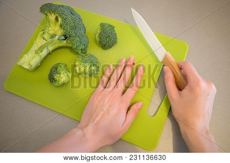 Wounded Finger With Blood And Knife On Cutting Board With Broccoli On Grey Background