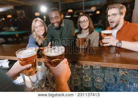 Cropped Image Of Barman Giving Beer To Multiculture Company Of Friends