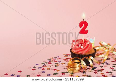 Second Birthday Cupcake With Candle And Sprinkles On Pink Background. Card Mockup, Copy Space. Birth