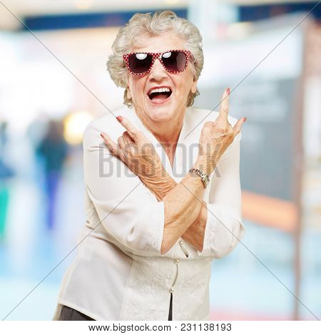 portrait of senior woman smiling and wearing sunglasses at crowded place