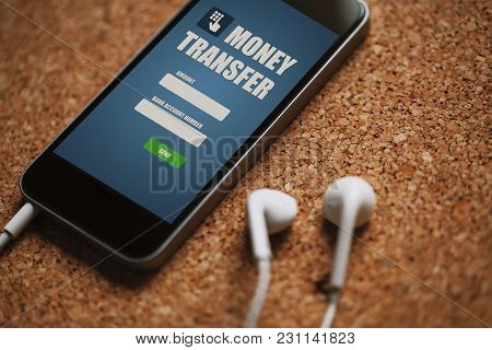 Mobile Phone With Money Transfer App In The Screen And White Earphones On A Cork Panel.