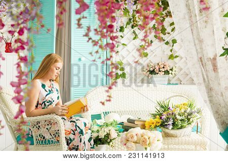 Young Woman Reading Interesting Book In Terrace Covered Beautiful Flowers And Plants In Warm Summer