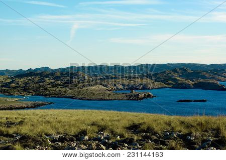 View From Cap De Cavalleria To Torre And Port De Sanitja On Blue Sky Background. Minorca, Balearic I