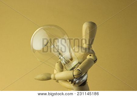 Wooden Person Holds Electric Bulb In Hand