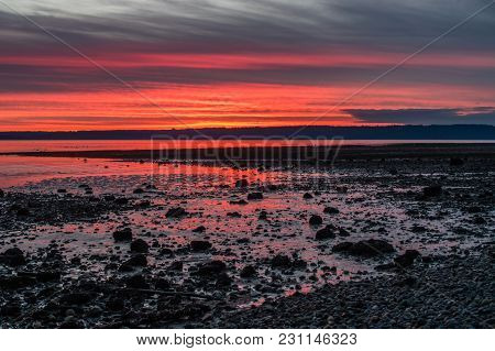 The Sun Sets Along The Shoreline In Burien, Washington.