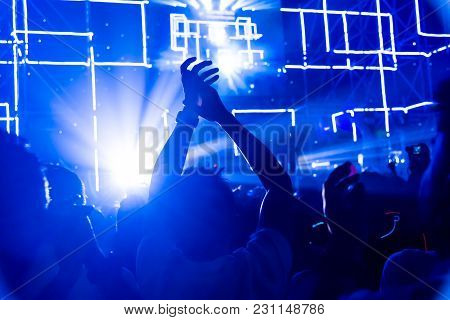 Crowd Of Hands Up Concert Stage Lights Enjoying Concert, And People Fan Audience Silhouette Raising