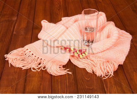 Thermometer, Glass Of Water, Tablets And Warm Scarf, Against Background Of Wooden Table