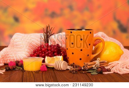 Cup Of Hot Herbal Tea With Lemon, Honey And Spices, Warm Scarf On Brown Wooden Table