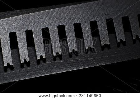 Closeup Of A Blade Of Thinning Scissors In The Dark Background.