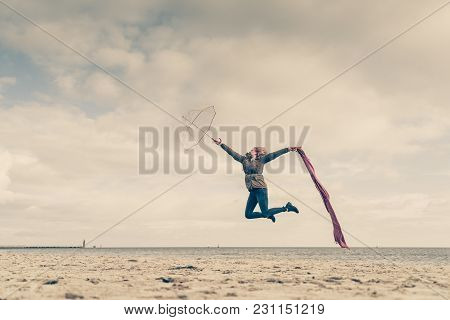 Happiness, Enjoying Weather, Feeling Great Concept. Woman Jumping With Red Scarf And Transparent Umb