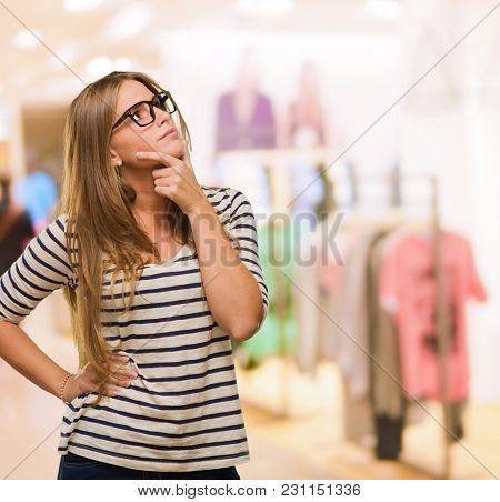 Young Woman Thinking at a clothes shop