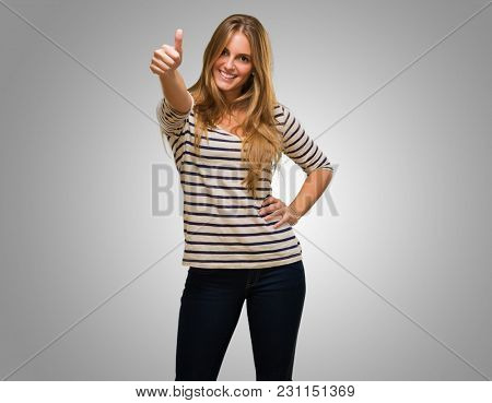 Young Woman Showing Thumb Up Sign against a grey background