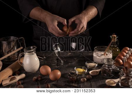 Set Of Ingredients And Baker's Hand Smash Eggs Into Bowl Isolated On Black