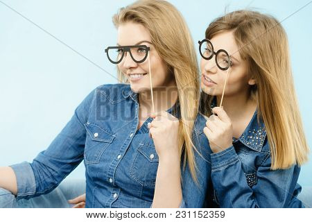 Two Happy Women Holding Fake Eyeglasses On Stick Having Fun Wearing Jeans Shirts. Photo And Carnival