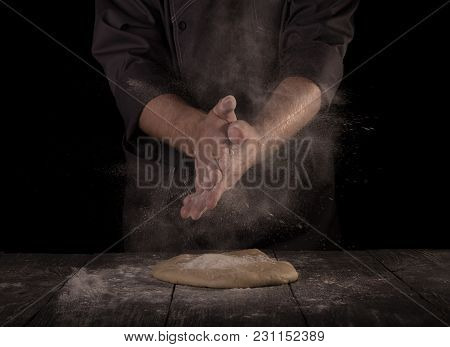Hands Of Baker Kneading Dough Isolated On Black Background