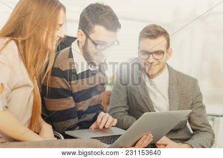 Closeup Of Friendly Business Team Working On Laptop And Discussing Business Matters.