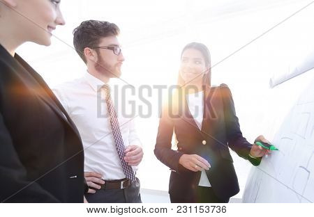 businesswoman pointing marker to flipboard on presentation in office
