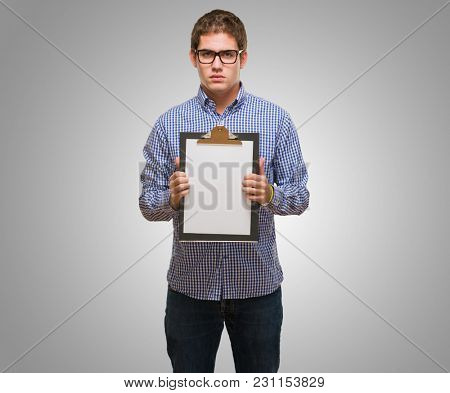 Businessman Showing Paper On Clipboard against a grey background