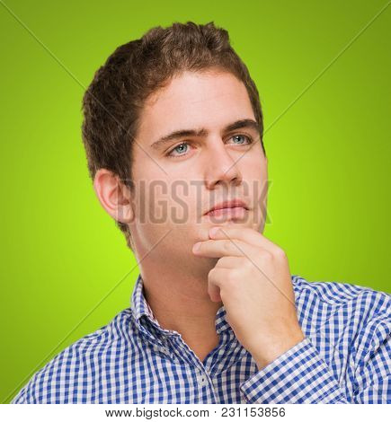 Portrait Of Young Man Thinking against a green background