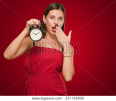Shocked Woman Holding Alarm Clock against a red background