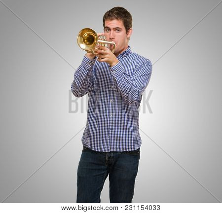 Young Man Blowing Trumpet against a grey background