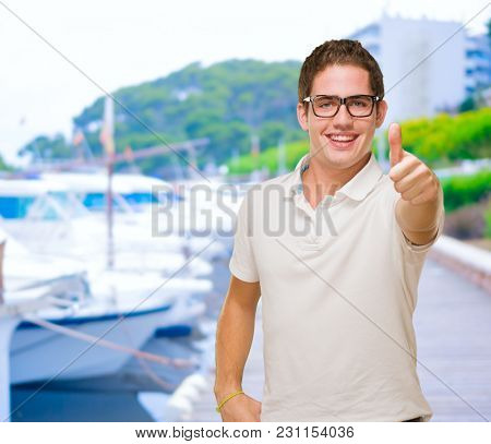 Young Man Showing Thumb Up at a port
