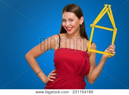 Happy Young Woman Holding House Frame against a blue background